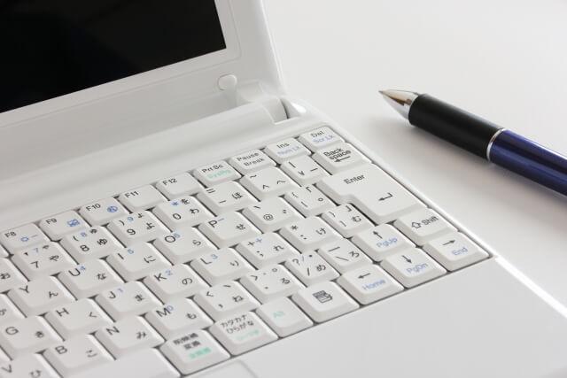 記事を書くためのパソコンとペン