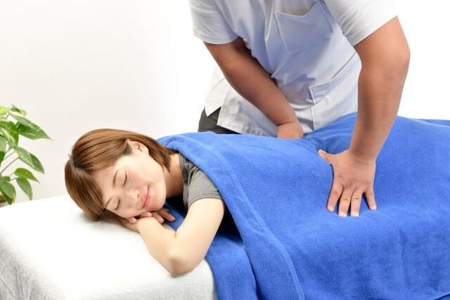 施術台に横たわりマッサージを受けている女性